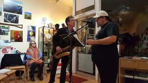 Ghost Town Poetry co-host Christopher Luna (right) introduces poet and musician Tim Jensen (center) while co-host and Luna's wife, Toni Pattington (left), watches on.