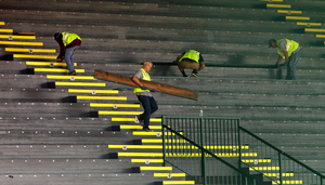 Workers remove seating planks from the East Grandstand at Hayward Field and take them to a truck for transport Monday, June 11, 2018, in Eugene, Oregon.