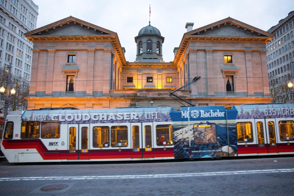 A TriMet MAX train glides past Pioneer Courthouse in downtown Portland.