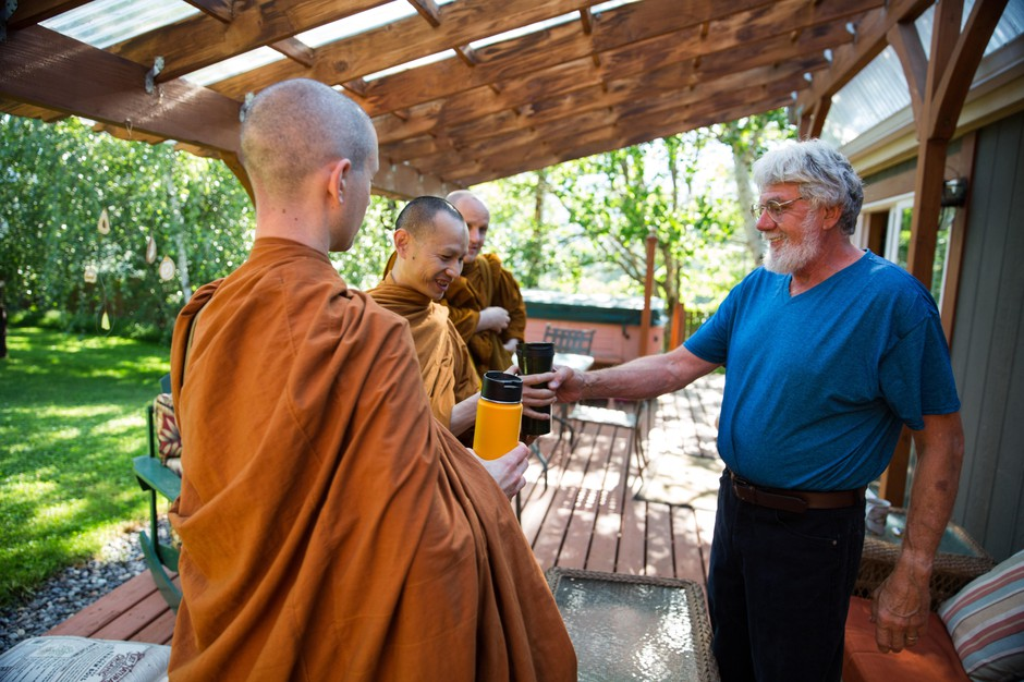 Ray Klebba, right, hands tea to Ajahn Kassapo on alms round. Klebba and his partner, Shelley Baxter, contribute food to the monks throughout the week.