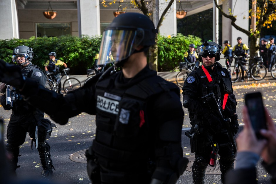 Portland police officers direct protesters back to Chapman Square Park, Portland, Oregon, Saturday, Nov. 17, 2018.