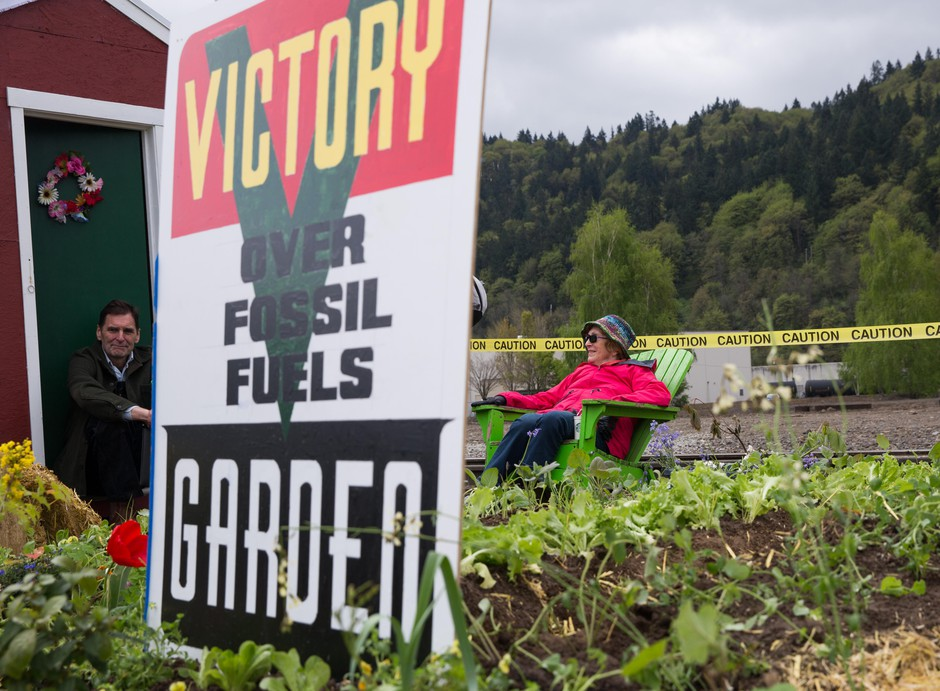 Activists with the environmental action group Extinction Rebellion, including Ken Ward, left, watch over a protest garden planted near the tracks of Zenith Energy's oil-by-rail terminal in Portland, Oregon, on Sunday, April 21, 2019.