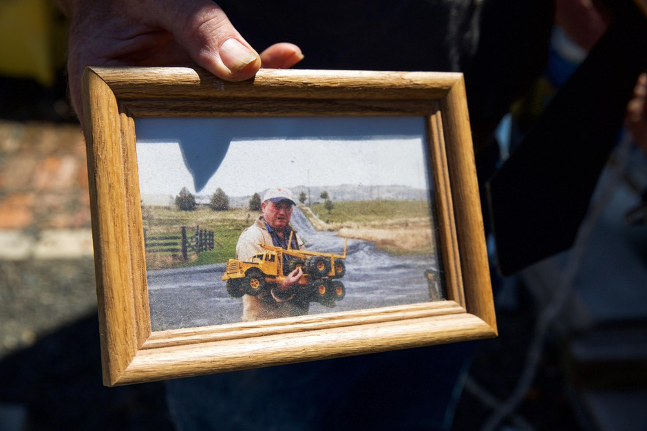 Otis Cody holds a framed photo of his father, Ray Cody, with a model truck like the ones Otis makes today in Fossil, Ore., Tuesday, June 4, 2019.