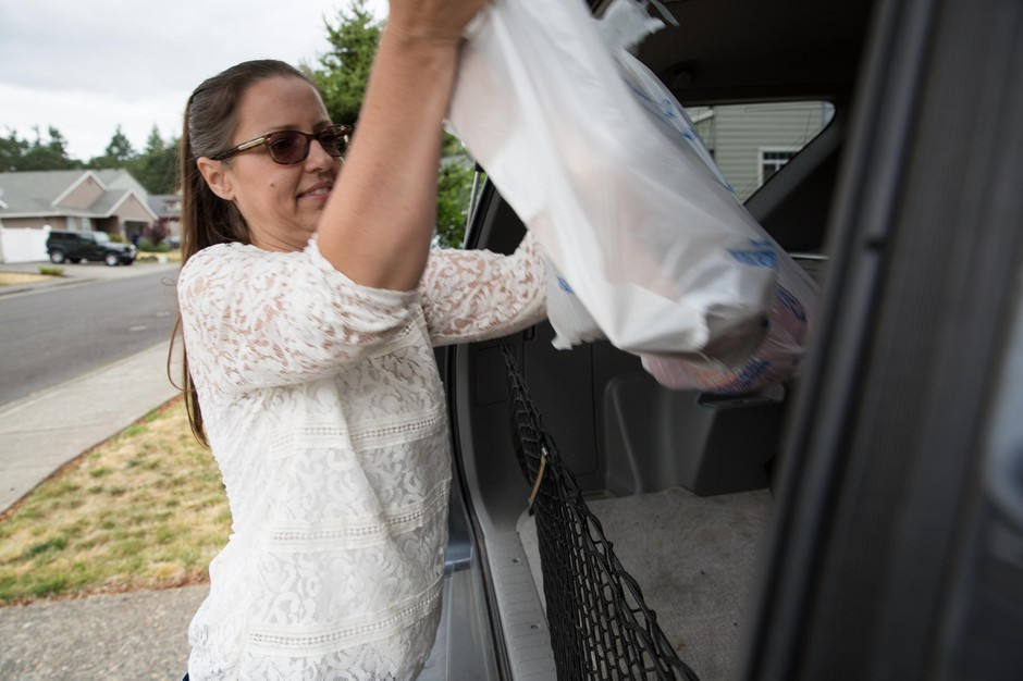 Michele King unloads grocery bags from her vehicle outside her home in St. Helens, Ore., on Friday, June 21, 2019.
