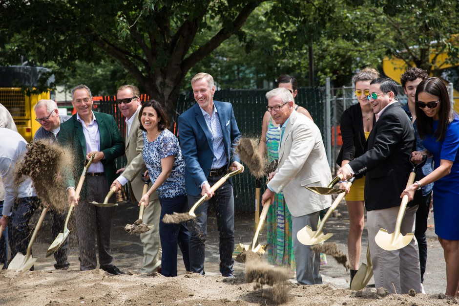 Mayor Ted Wheeler, center, blue suit, and others break ground at the site of a future Ritz-Carlton luxury hotel in Portland, Ore., Friday, July 12, 2019. The hotel has displaced the Alder Food Carts, which had occupied the space since the late 1990s.