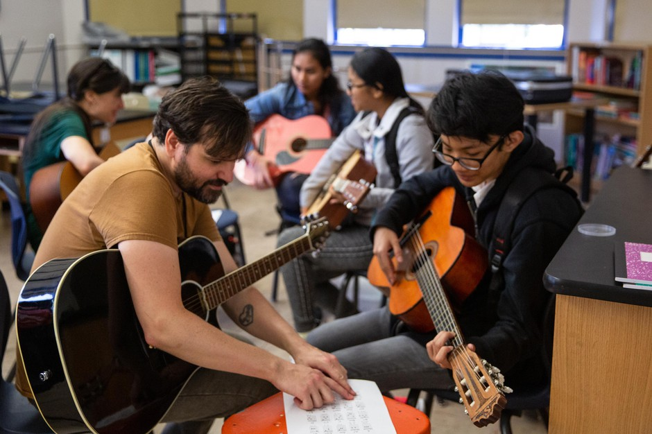 Wilson Vediner, left, teaches a student chords on the guitar at the Pass the Mic workshop at Hosford Middle School in Portland, Ore., Monday, July 29, 2019. Vediner, who's played in bands like Months and Point Juncture, WA, is the workshop's program director.