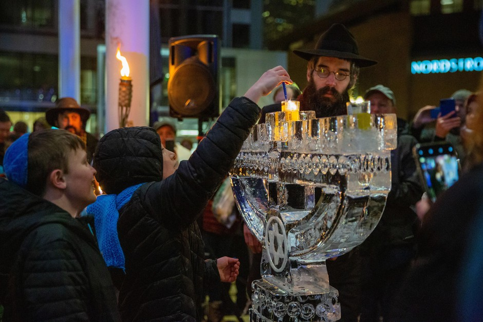 Rabbi Motti Wilhelm, right, watches as children light a candle using the flame from the menorah at Director Park for the first night of Hanukkah on Sunday, Dec. 22, 2019, in Portland, Ore.