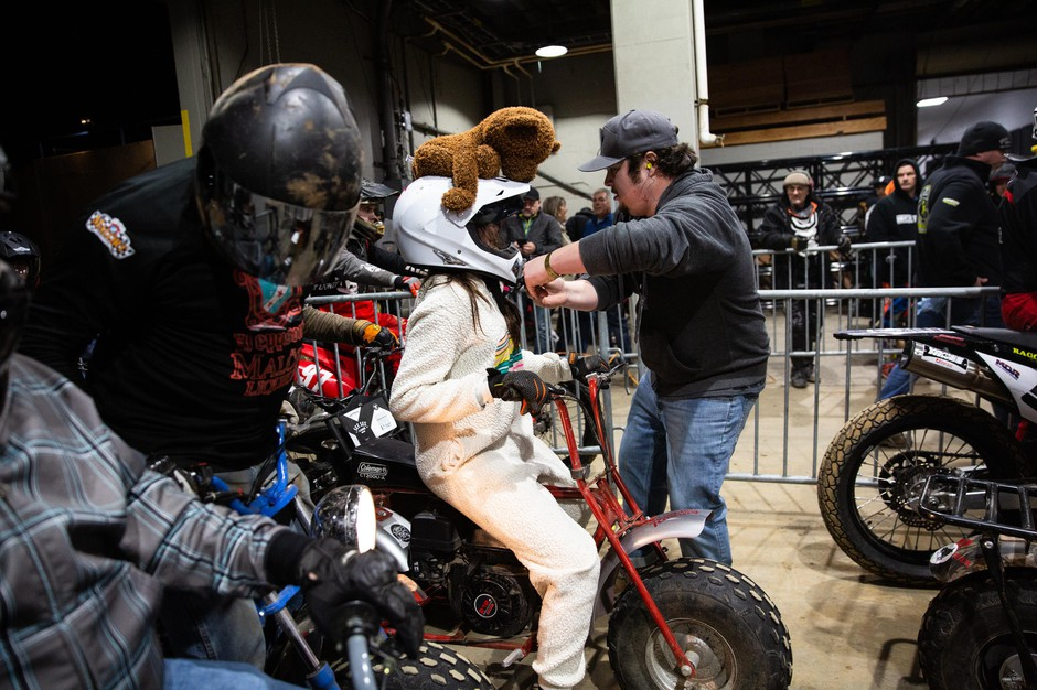 A worker affixes a camera to a racer's helmetbefore the costumed heat at the One Pro Race.