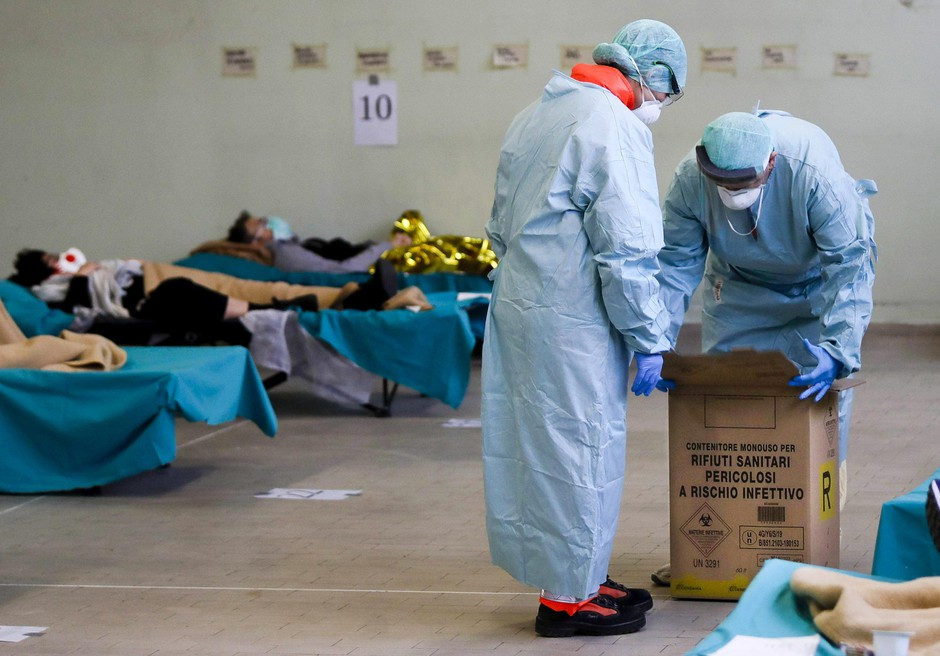 Paramedics carry a hazardous medical waste box as patients lie on camping beds, in one of the emergency structures that were set up to ease procedures at the Brescia hospital, northern Italy, Thursday, March 12, 2020.