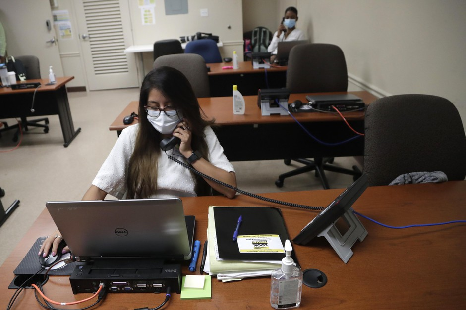 In this Wednesday, May 13, 2020 photo, Maria Fernanda works on contact tracing at the Florida Dept. of Health in Miami-Dade County, during the new coronavirus pandemic, in Doral, Fla. In state after state, the local health departments charged with doing the detective work of running down the contacts of coronavirus patients are falling well short of the number of people needed to do the job.