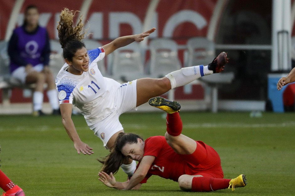 n this Feb. 7, 2020, file photo, Costa Rica forward Raquel Rodriguez, top, is knocked over by Canada defender Allysha Chapman during the first half of a CONCACAF women's Olympic qualifying soccer match in Carson, Calif.