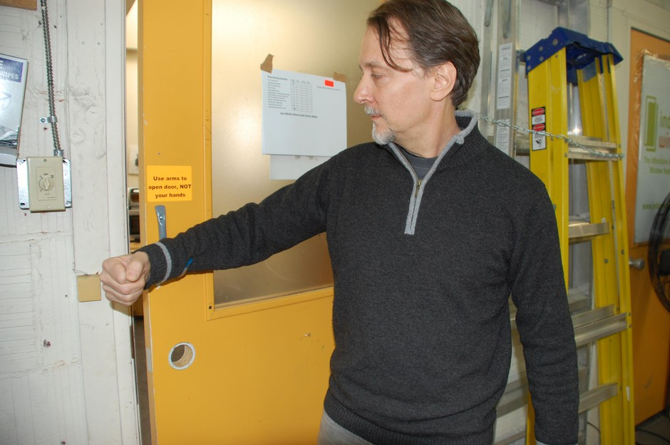 """Coronavirus adaptation: Indow CEO Sam Pardue demonstrates how to pull the factory door open with an elbow. """"We don't want people using doorknobs anymore at all,"""" he said."""