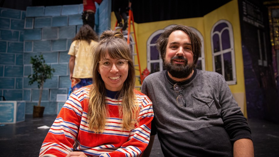 "Writer and director Megan Tabaque (left) with producer Zack Traeger (right), sitting on the Revolution Hall stage where their satirical, rock musical, ""Batman Returns Returns,"" is getting its Portland premiere."