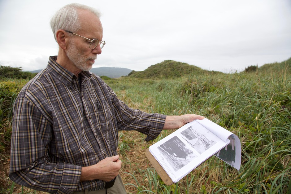 Historian Jerry Sutherland looks at old pictures of Bayocean as he walks the dunes in search of the town that used to stand under his feet.