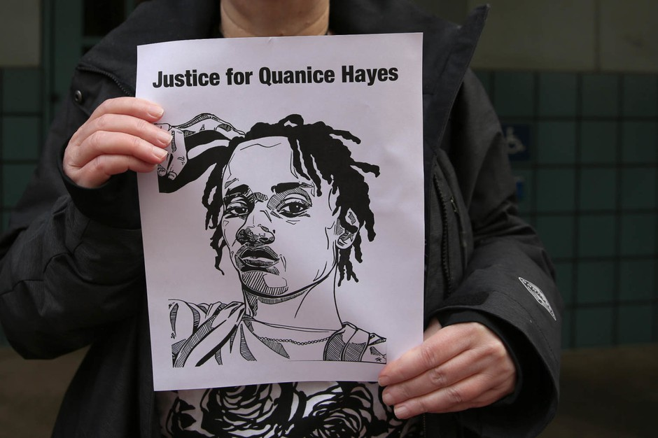 An activist with Don't Shoot PDX stands downtown after a grand jury declined to charge a police officer in the shooting death of Quanice Hayes.