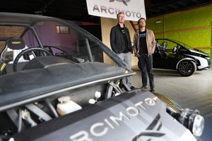 Arcimoto president Mark Frohnmayer and business development lead Jesse Fittipaldi stand among the previous generations of the Arcimoto electric vehicle.