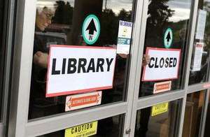 Staff members tape a closed sign to the front door to the Douglas County Library Roseburg branch in May. The branch closed due to budgetary reasons, leaving the city of Roseburg without a public library branch of its own.